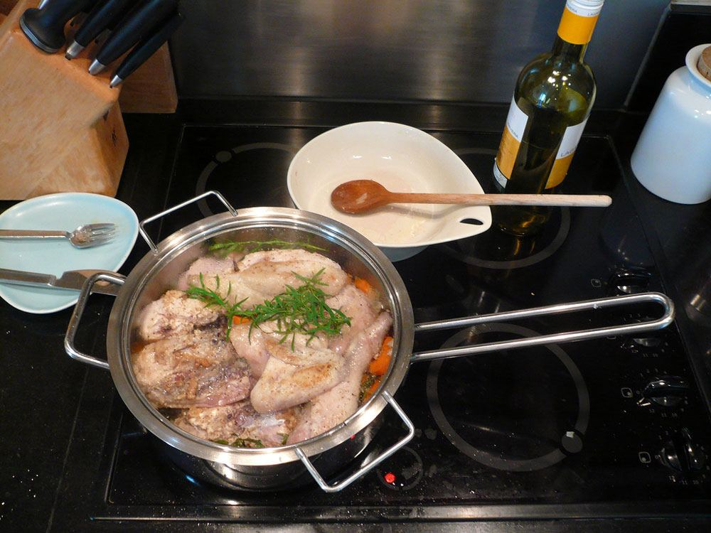 a chicken pot on the gas stove, knife, fork, spoon and a bottle of wine on the table