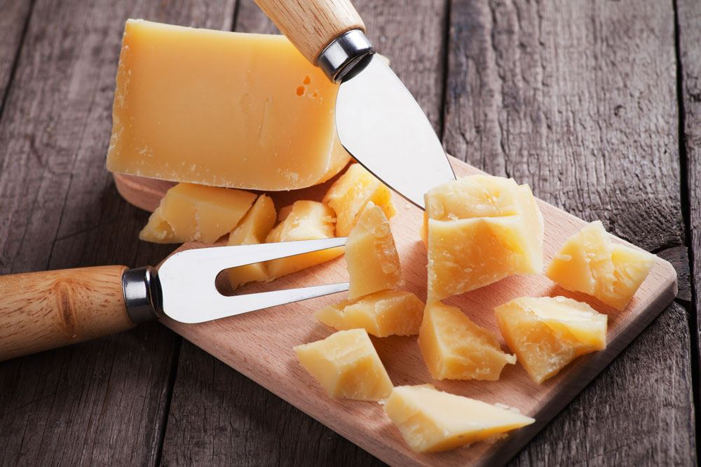 Sliced Grana Padano, a knife and a fork on the chopping board