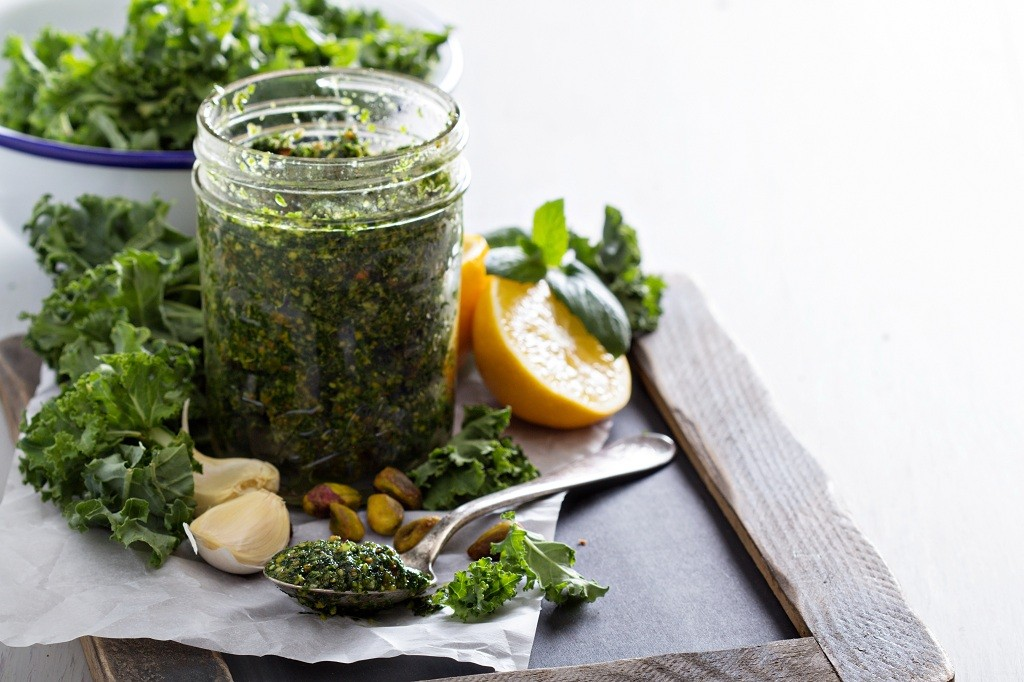 A bottle of A bowl of Kale Pesto, a bowl of Kale Pesto and a spoon of Kale Pesto