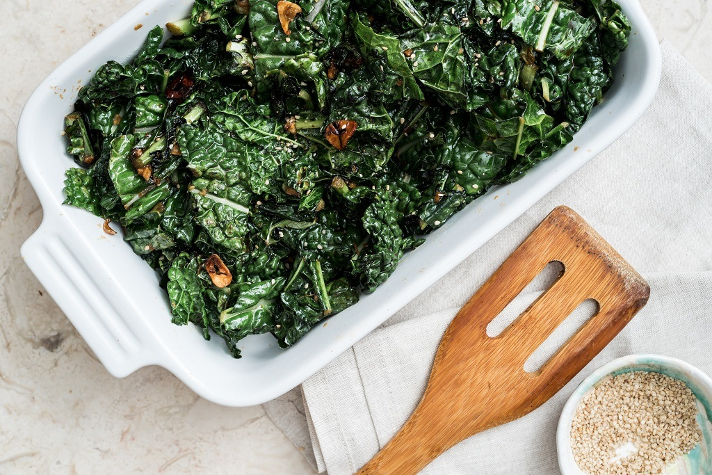 Braised kale on the plate and a spoon
