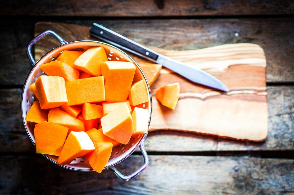Pieces of Butternut Squash and a knife on the chopping board