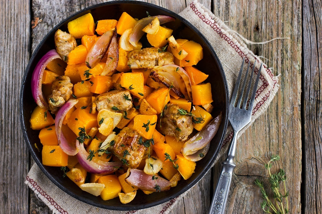 A pot of Butternut Squash with sliced onions and a spoon