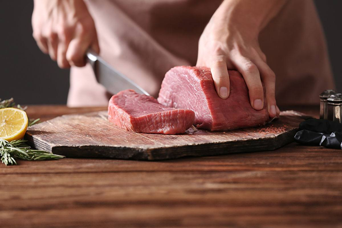 A man uses the butcher knife to cut the meat on the chopping board