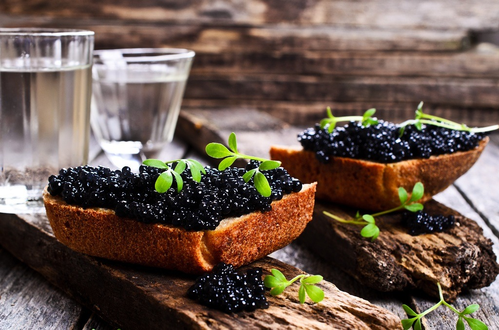 Pieces of bread with caviar and cheese and cups of water
