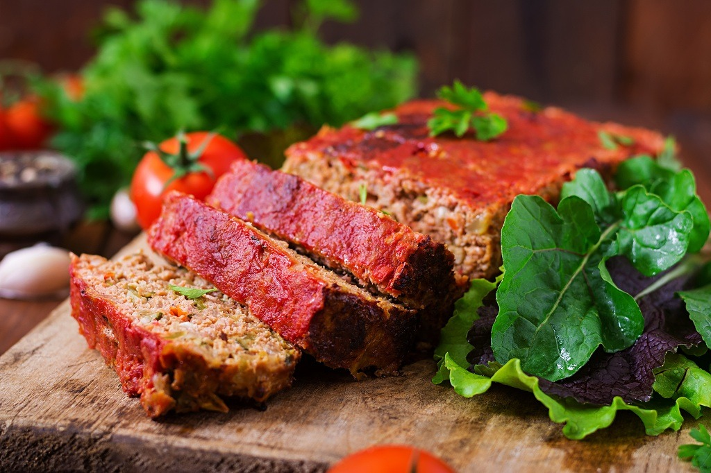 meatloaf and vegetables on the chopping board