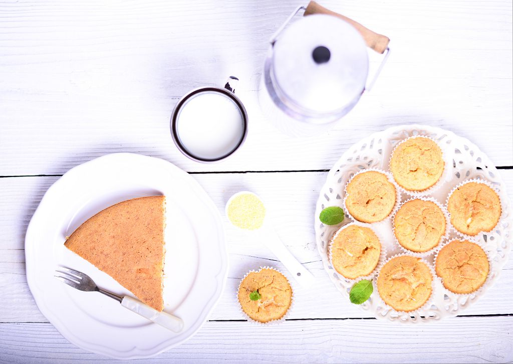 Cornbread and a fork on plate, milk and a plate of Cornbread