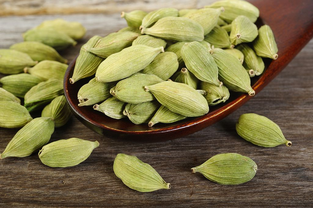 a spoon of cardamom and cardamom on the table