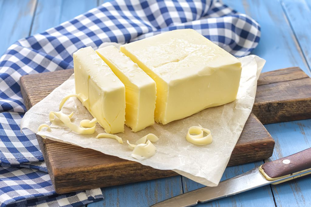 butter and slices of butter on the chopping board and a knife