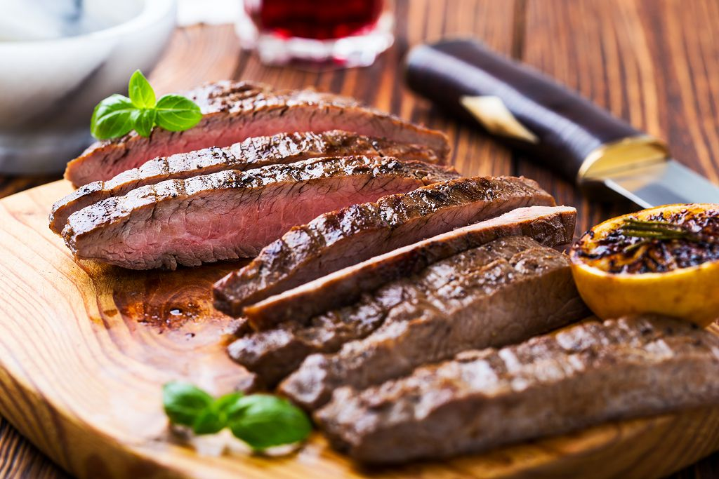 Slices of beef steak on the chopping board and a knife