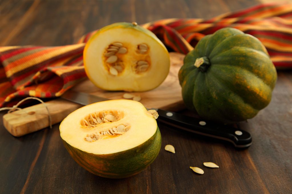 an acorn squash, a knife and sliced acorn squash on the chopping board