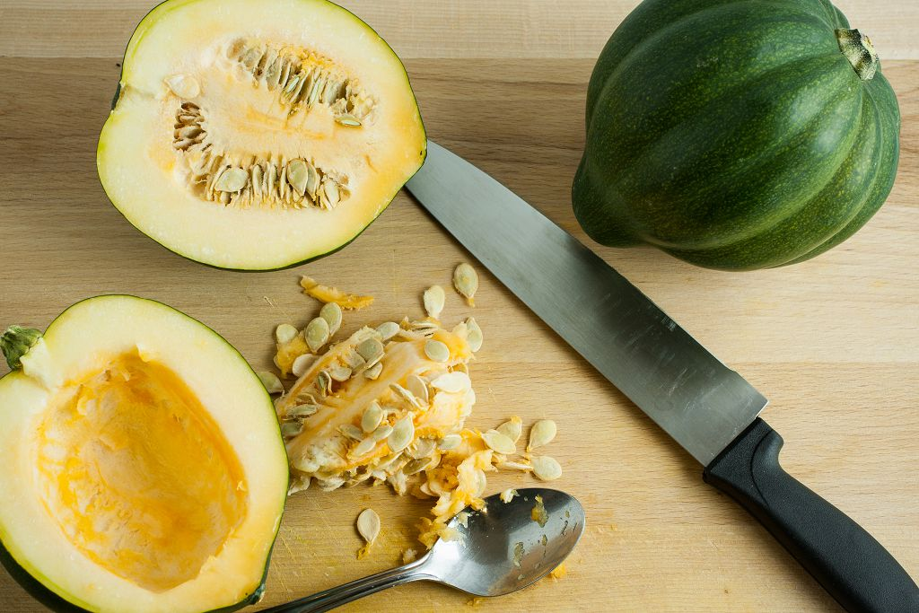an acorn squash, a knife and sliced acorn squash