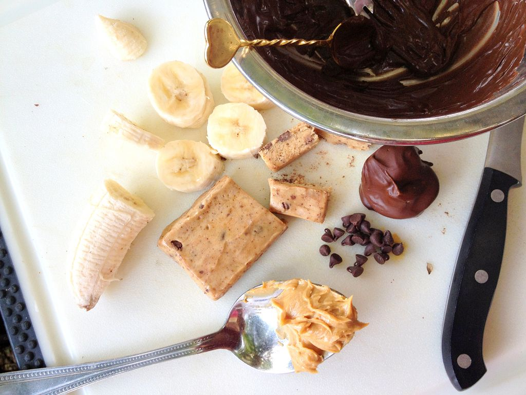 a bowl of melt nutella, sliced bananas, a knife and a spoon
