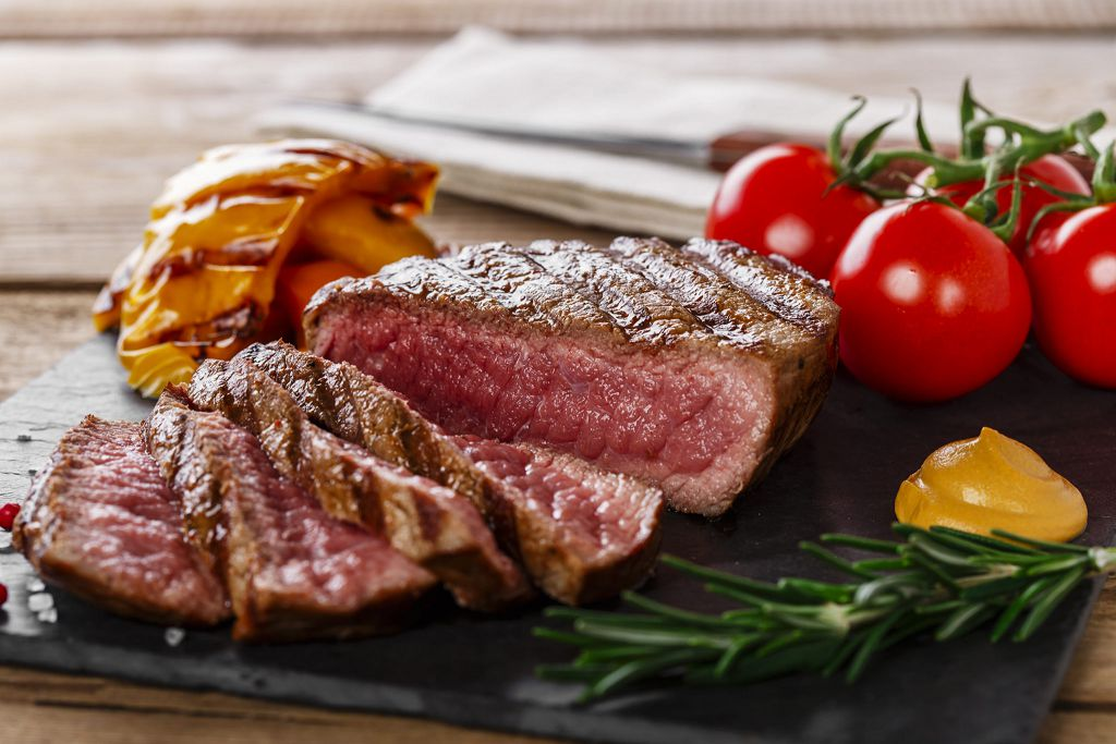 Slices of Beef Steak and tomatoes on the chopping board