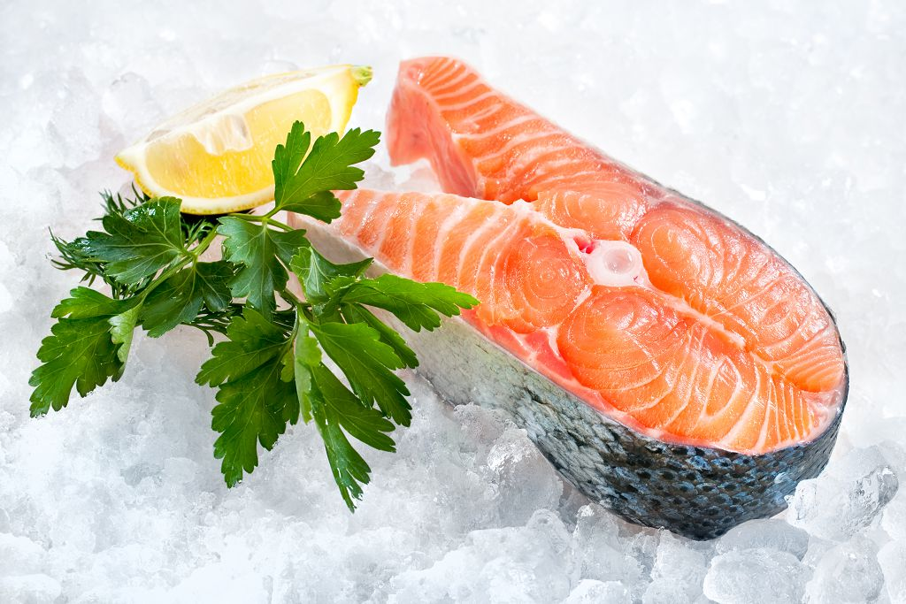 pieces of fresh salmon and sliced lemon on the ice
