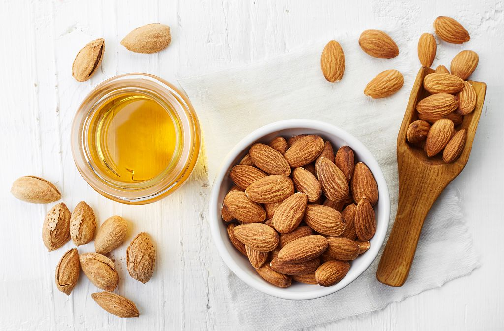 A bowl of Almonds, a spoon of Almonds and Almonds