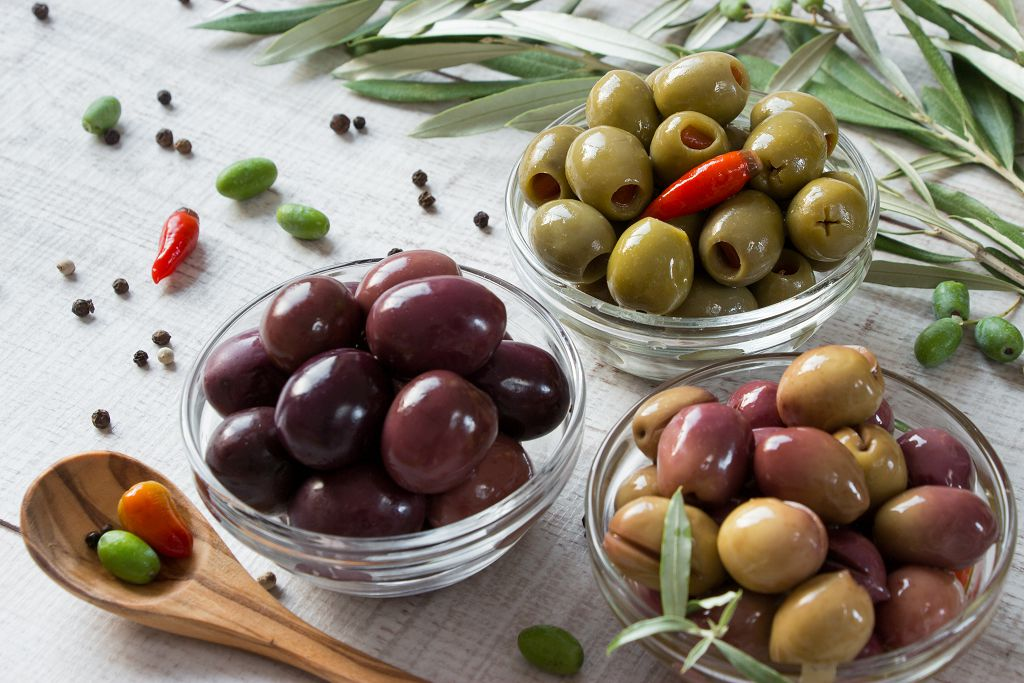 Bowls of Olives and a spoon of Olives