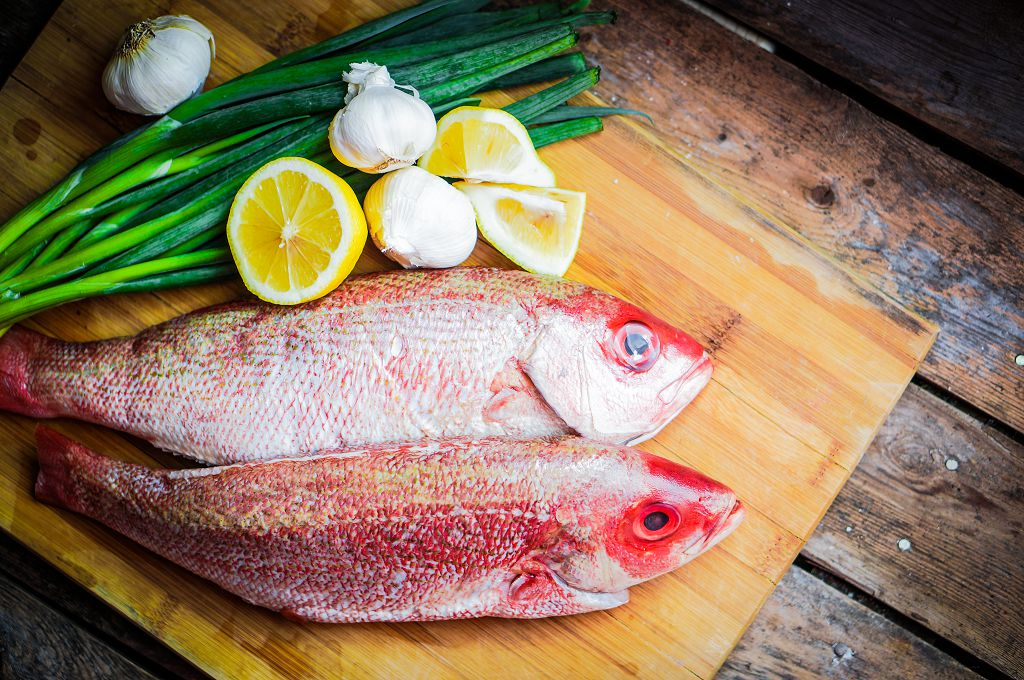 Fresh Snapper, slices of lemon and scallions on the chopping board