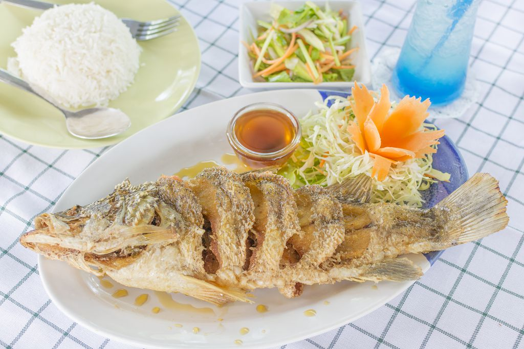 Lightly-Fried Snapper,  fish sauce and vegetables on the plate, rice, a spoon and a fork