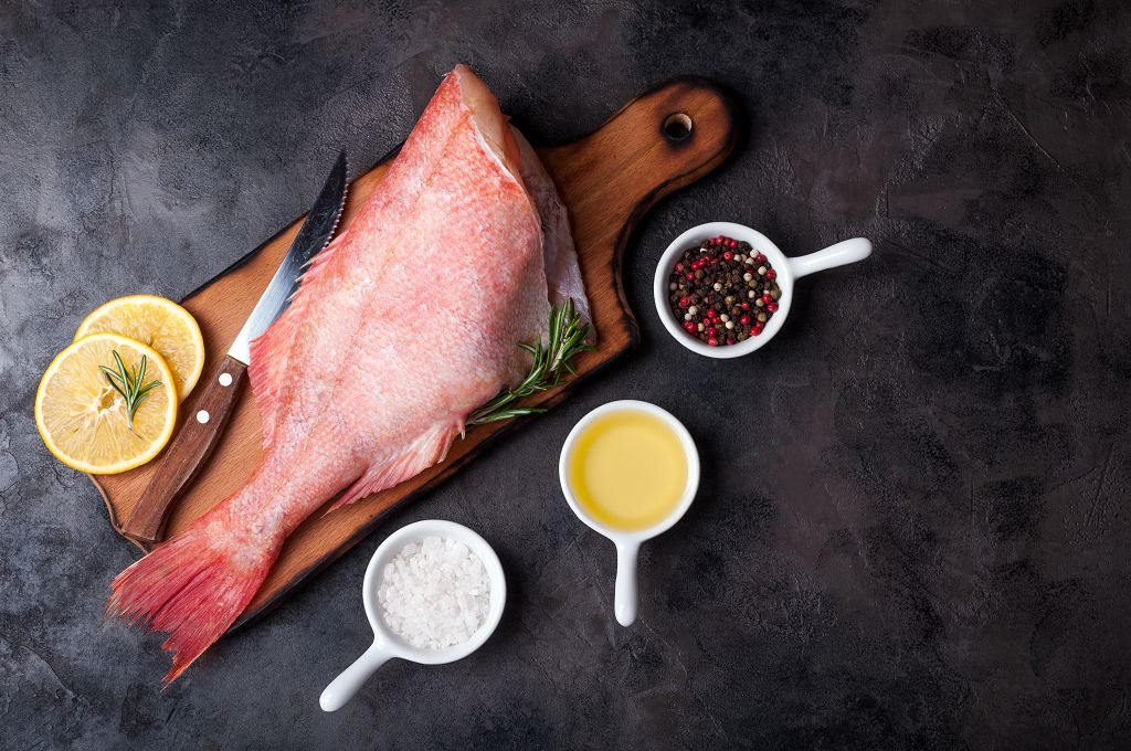 Fresh snapper, knife,  slices of lemon on a cutting board and spices