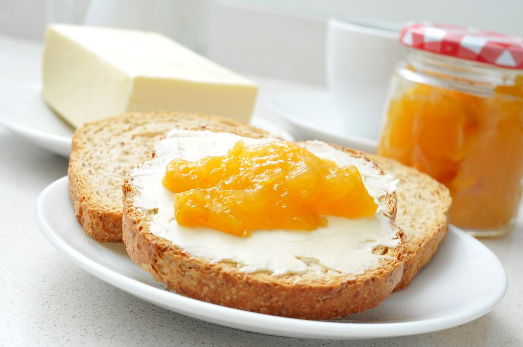 bread with peach jams and butter on the plate