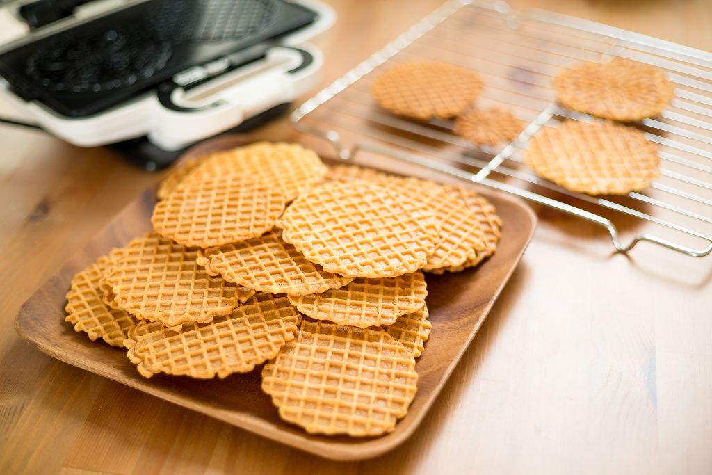 A Pizzelle Maker and pizzelles  on the tray