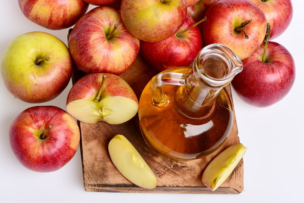 A jar of Apple Juice  and Apple on the chopping board