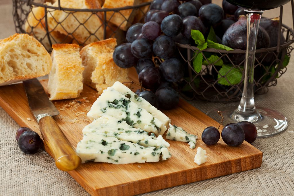 Blue Cheese, grape, slices of bread and a knife on the chopping board