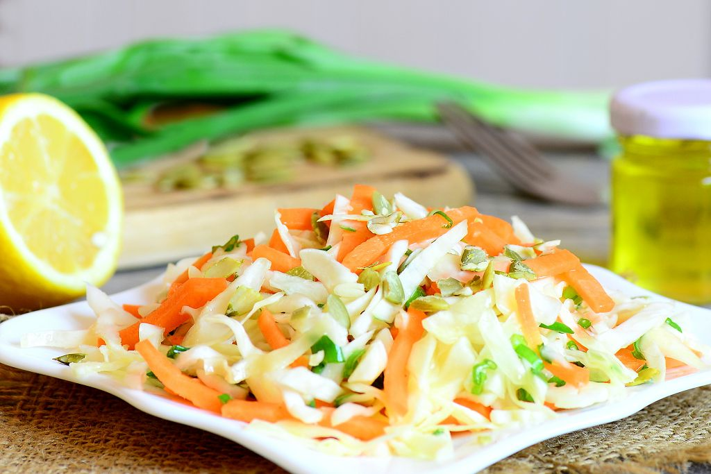 A plate of Coleslaw and slices of lemon