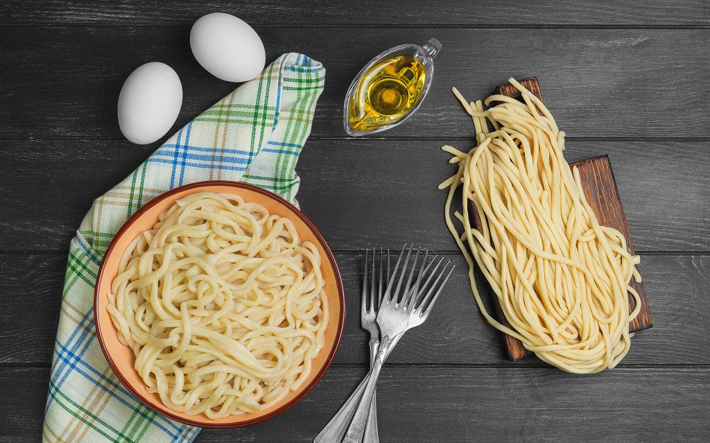 cooked spaghetti, Pasta sauce, eggs and forks on the table