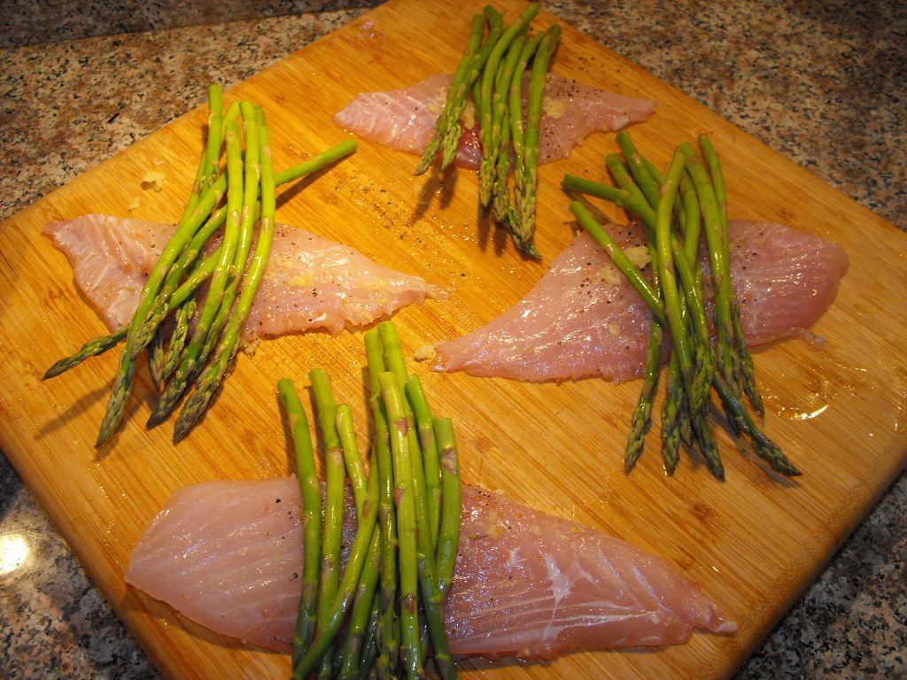 Slices of triggerfish and asparagus on the chopping board