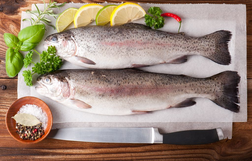 trouts and slices of lemon on the chopping board and a knife