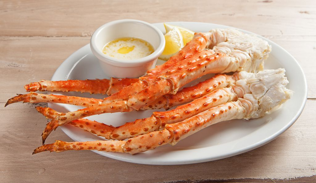 A plate of crab legs and slices of lemon