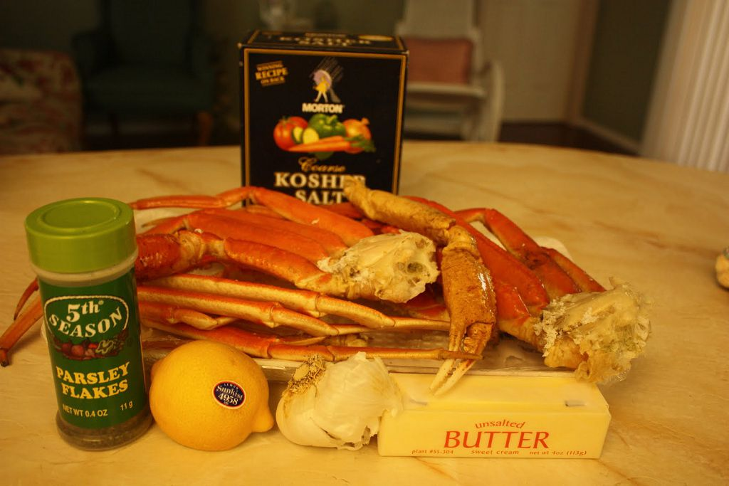 A plate of crab legs, lemon, garlic head and Butter