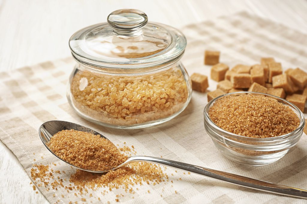 A jar of  Brown Sugar, a bowl of  Brown Sugar, a spoon of  Brown Sugar and  Brown Sugar on the table