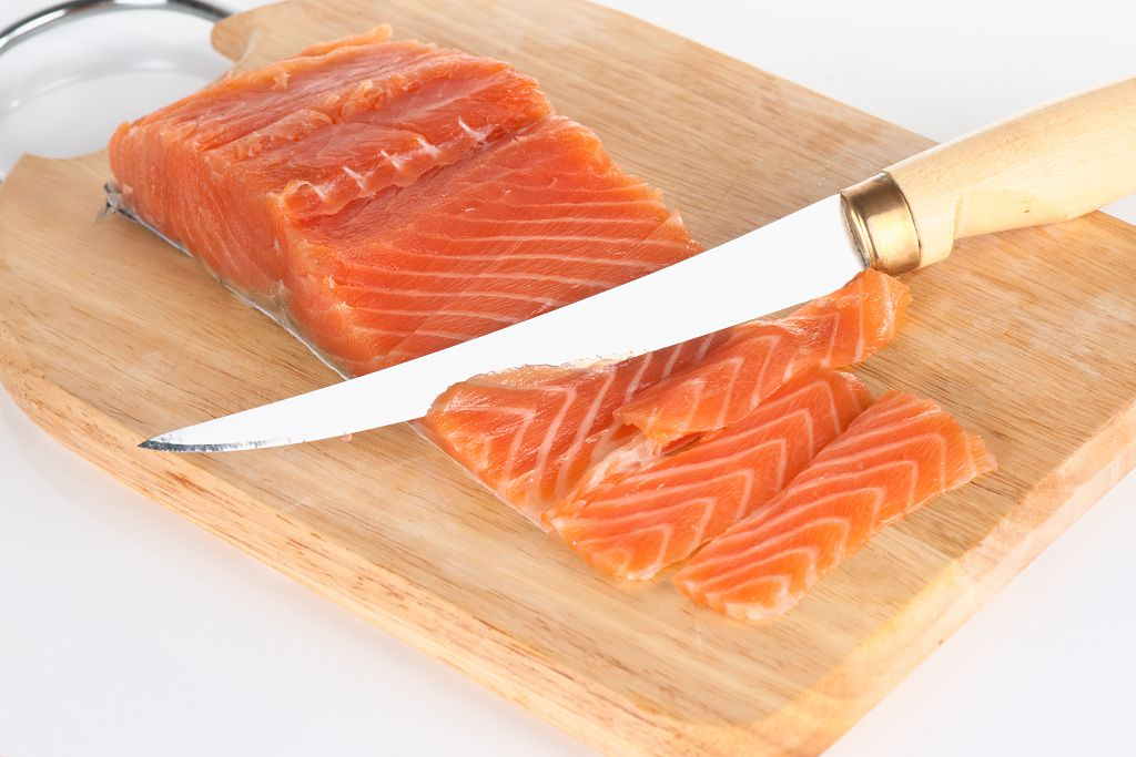 slices of salmon and a knife on the chopping board