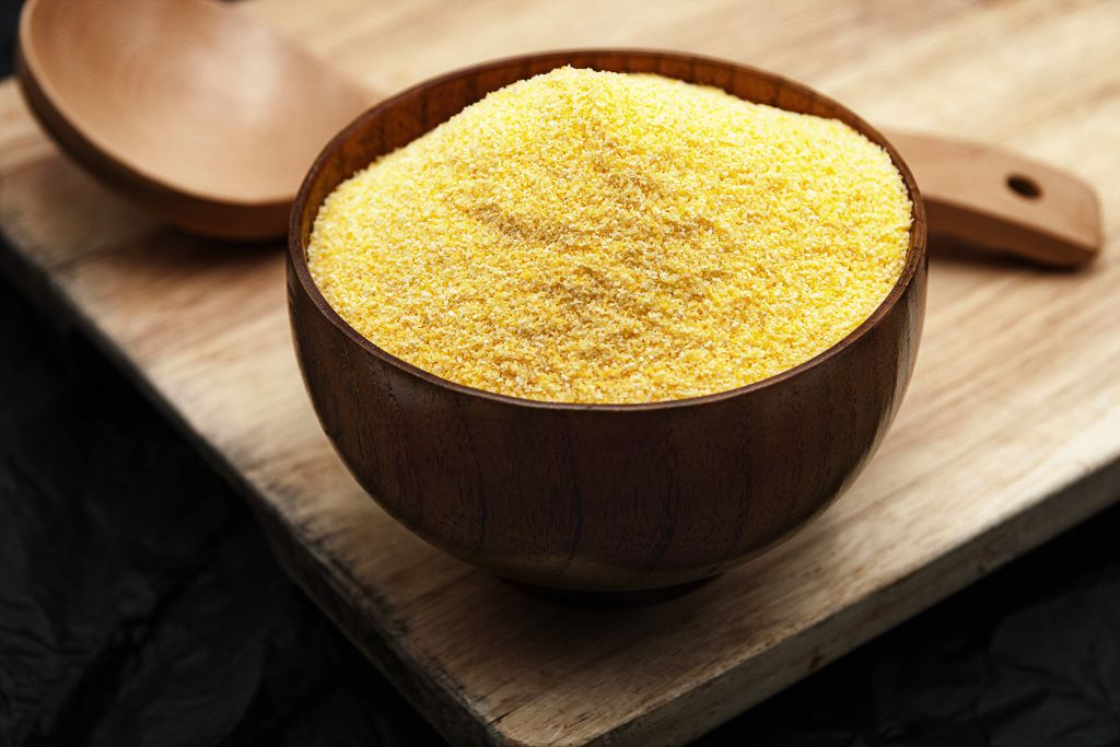 A huge bowl of Cornmeal and a big spoon on the table