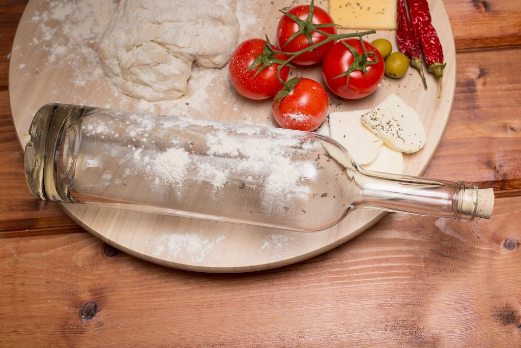 a wine bottle, flour and fruits on the chopping board