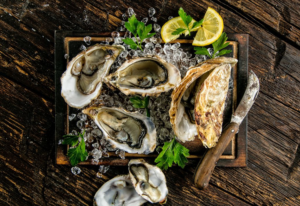 Oysters, a knife and slices of lime on the tray