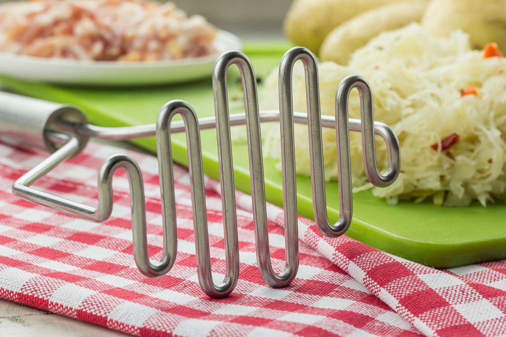 A Potato Masher and vegetables on the table