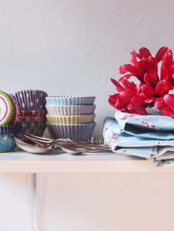 Colorful cupcake wrappers over a shelf in a rustic kitchen