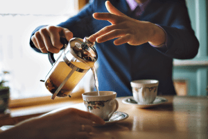 Man pouring herbal tea in a mug of French press.