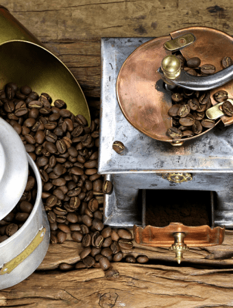 coffee grinder with manufacture roasted Indonesian Arabica coffee beans on rustic wooden background