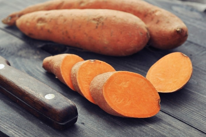 Sliced Raw Sweet Potatoes, a knife and Sweet Potatoes