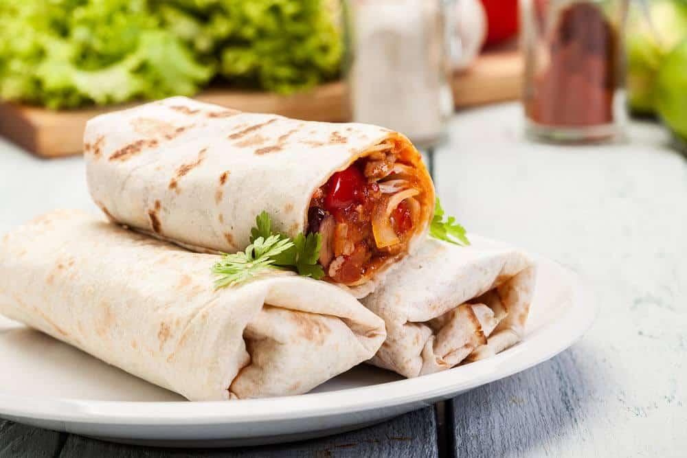 A plate of wraps and vegetables on the table