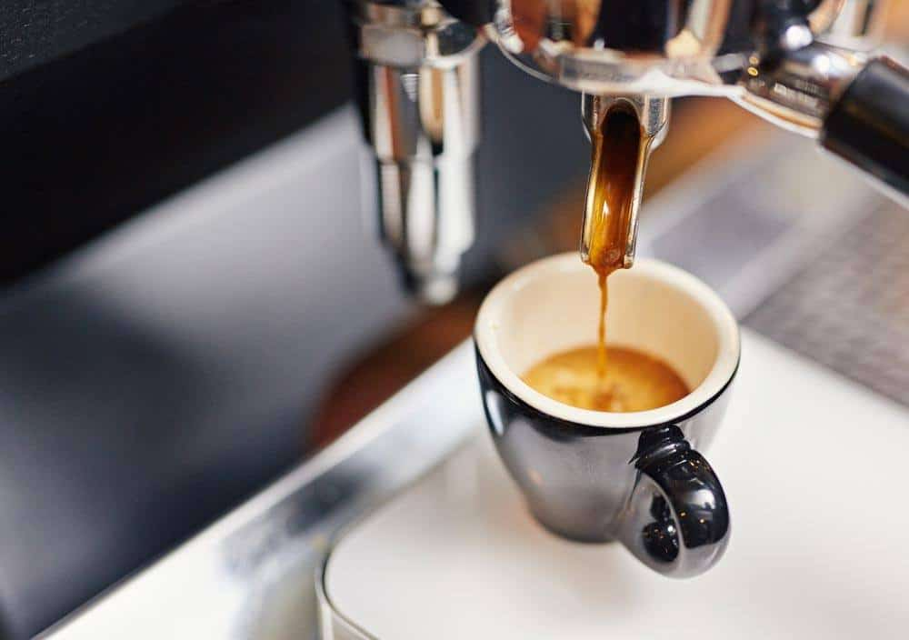 A cup of Espresso and coffee maker
