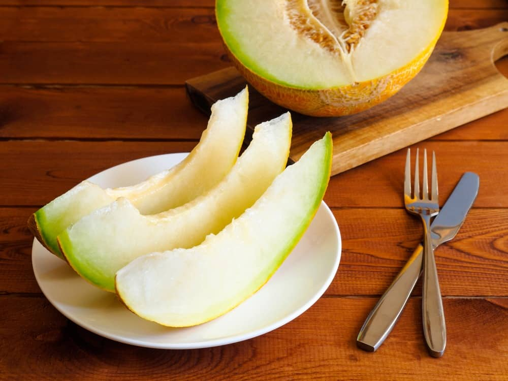 slices of honeydew melons on the chopping board and a plate of slices of honeydew melons