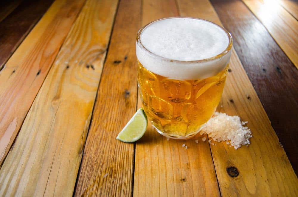 A cup of beer, slices of lime and salt
