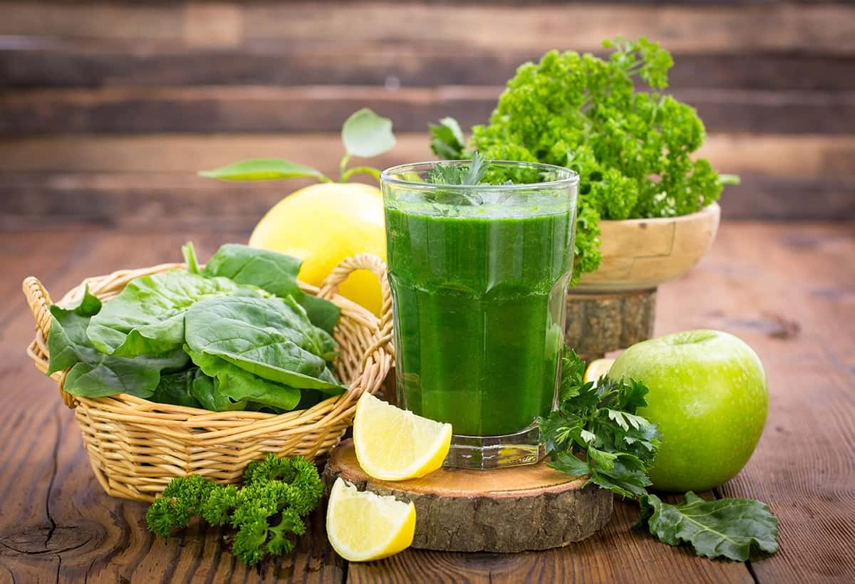A cup of Romaine Lettuce-Apple Green Smoothie and fruits