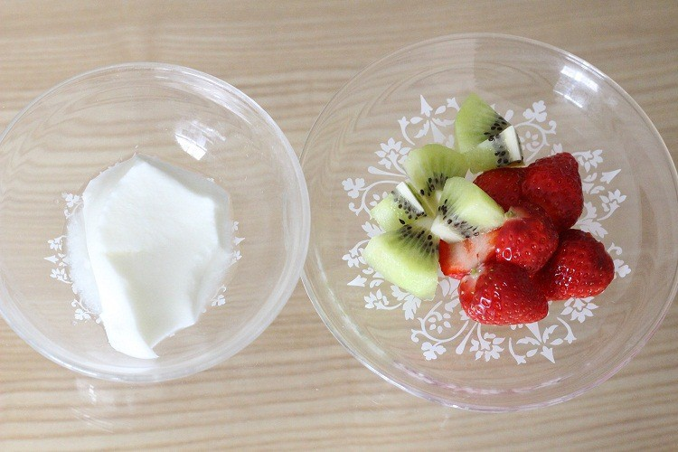 A bowl of Yoghurt and a bowl of fruits